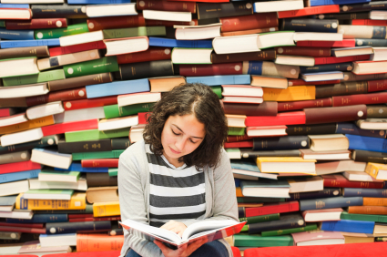 A women reading with a pile of books behind her